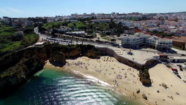 People on beach near cliffs Lagos aerial view video