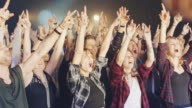 People on concert waving and clapping hands video