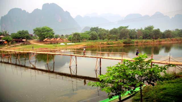 People passing bamboo bridge on limestone mountain background video