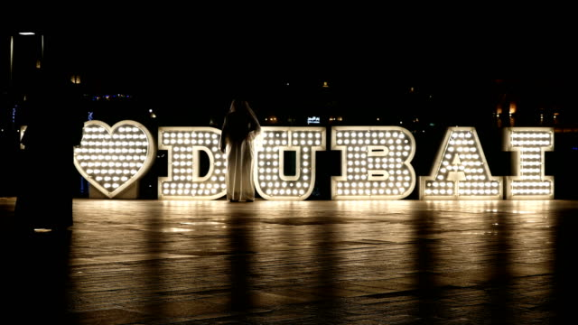 People passing by in front of lighted 'I love Dubai' logo at night, 4k video