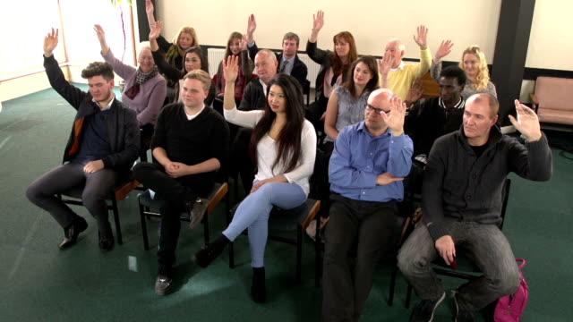 People raising hands in meeting - CRANE HD video