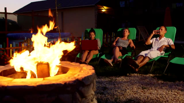 People relaxing in back yard sitting on patio loungers near fire pit at dusk video