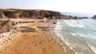 People rest on the beach naer Zambujeira de Mar, Portugal aerial view video