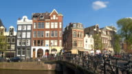CLOSE UP: People riding bicycles in crowded Amsterdam old town on sunny day video
