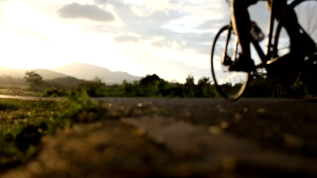people riding bike outdoors in park at sunset, fitness, sport and exercise, healthy life and lifestyle concept. video