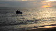 People riding jet ski on the beach in twilight video