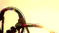 SLOW MOTION CLOSE UP: People riding roller coaster at sunset video