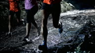 SLO MO DS People running on a muddy forest trail at night video