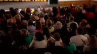 People seated in an audience and applauding video