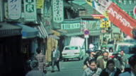 1972: People shopping at outdoor Japanese marketplaces and city streets. video