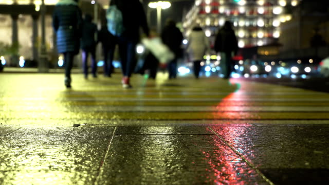 People silhouettes n the lights of night city on a crosswalk. Pedestrians sleet video