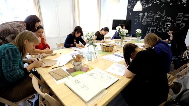 People sit around wooden table in art studio on seminar video