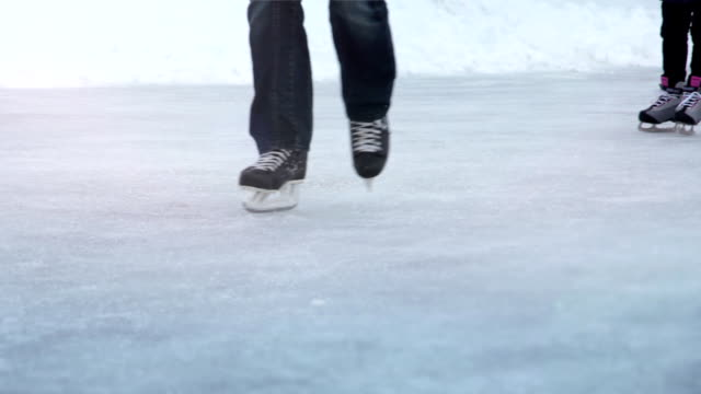 People skating toward the camera, through a sun flare (Loopable) video