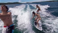 People surfing behind a boat, third one jumps into sea video