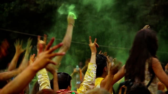 People throw colorful paint in the air at festival, celebration video