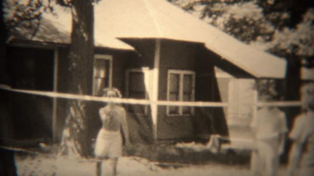 1936: People throwing floppy frisbee disc over badminton net. video