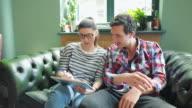 People using digital tablet in coffee shop. video