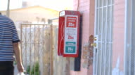 People Walk by Red Pay Phone in Border Town video