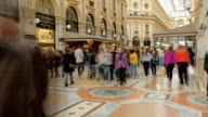 People walk on Duomo square near the famous Vittorio Emanuele shopping gallery, Milan city, Italy. video