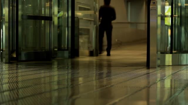 People walk through revolving door at airport video