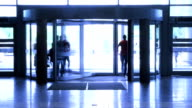 People walk through revolving door video