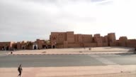 People walking and cars passing by in front of the outer walls of the front façade of Kasbah Taourirt video