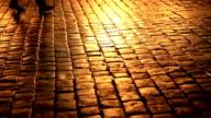 People walking in a cobblestone street at night video
