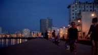 People walking in The Malecon at sunset in La Havana city in Cuba. video