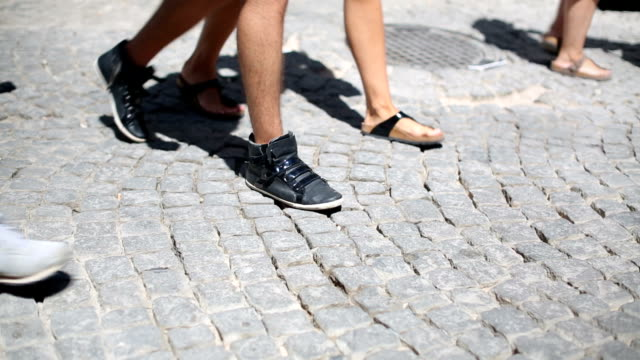 People walking on cobbled stone pavement video