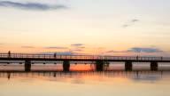 People walking on pier at sunset video