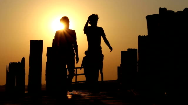 People Walking Over Wooden Bridge in Sunset 1 video