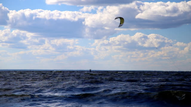 People windsurfing kiteboarding. Static landscape panorama shot with low clouds at sunny weather video