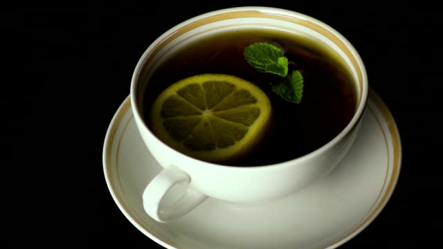 A peppermint leaves falls into the tea. Slow motion video
