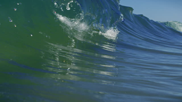 A perfect clear wave breaks over camera in POV on shallow sand beach in the California summer sun. Shot in slow motion on the Red Dragon at 150FPS in 4K. video