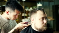 Perfect trim. Rear view close-up of young bearded man getting haircut by hairdresser with electric razor while sitting in chair at barbershop video