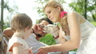 CLOSE UP: Perfect young family with baby and small dog enjoying picnic in park video