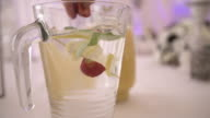 Person adding strawberry in refreshing drink at wedding video
