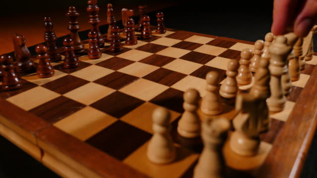 A person brings a white king to the center of the chess board and lies him down as a sign of surrendering video