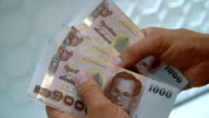 Person counting Thai baht. video