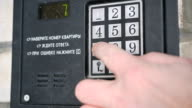 Person dialing number of apartment on a doorphone video