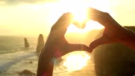 Person frames Twelve Apostles at sunset into heart shape video