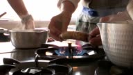 Person heating vegetable ginger on fire stove video