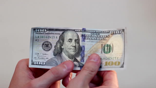 Person holding in hands and turning over one hundred-dollar bill video