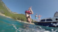 POV Person in water watching friend jump from boat video