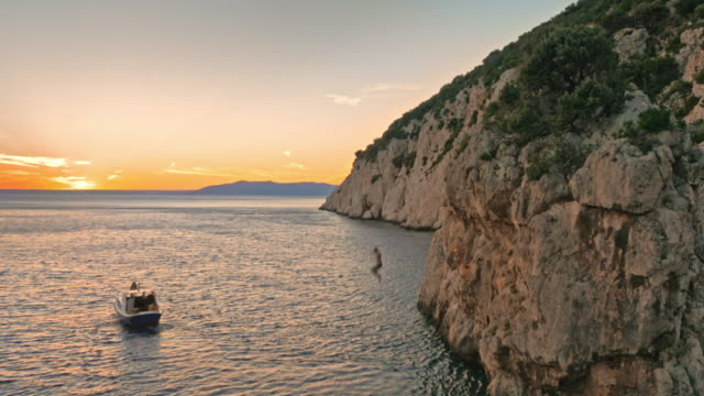 AERIAL Person jumping off cliff into sea at sunset video