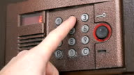 Person pushing buttons on the panel of intercom video