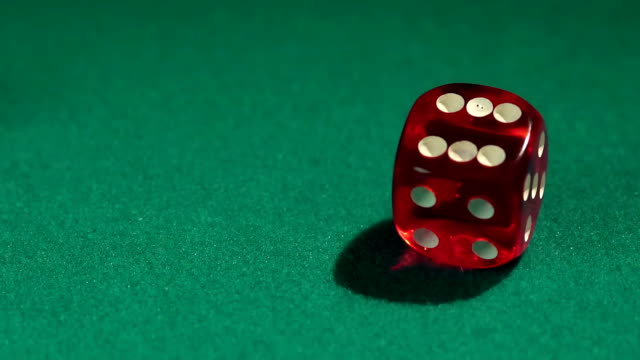 Person rolling dice on green casino table, closeup. Addiction to video