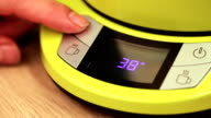 Person setting electric tea kettle temperature to 60 C (140F) video