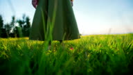 Person stand in grass at sunset low angle video