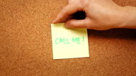 Person sticking a note reading 'Call me' on a cork board video
